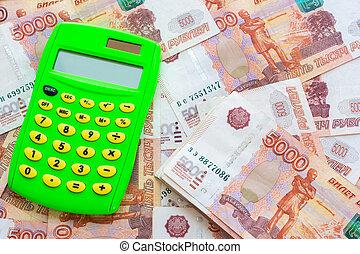 Green calculator and a bunch of five thousandth bills