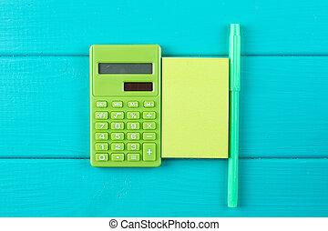 green calculator with a paper sticker