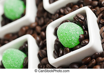 View of green candies and coffee beans in coffee cup.