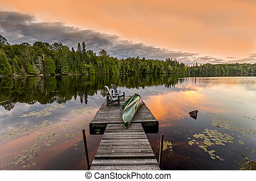 Green Canoe and Chairs on a Dock at Sunset