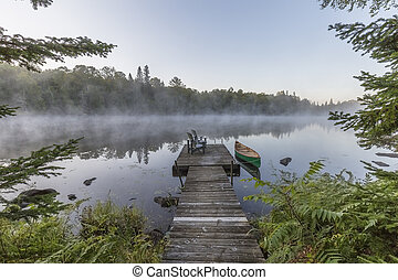 Green canoe tied to a dock on a misty morning - Ontario, Canada