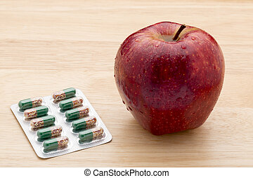 Green capsules bliter pack and fresh red apple