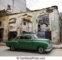 Green classic american car in havana street with eroded buildings in the background