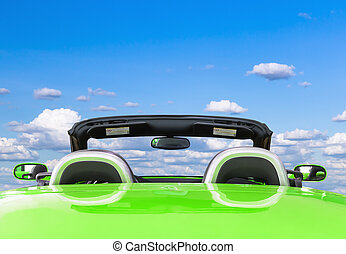 Green car with blue sky background