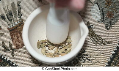 Green cardamom is grinded in a ceramic mortar using a pestle