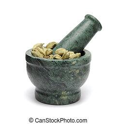 Green cardamom on marble pestle.