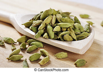 Green Cardamom Pods on wooden background closeup