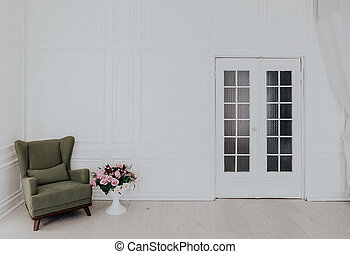 Green Chair in a white room with a door