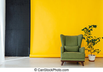 green chair in the interior of the room with a yellow background