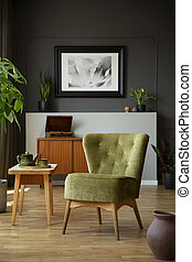 Green chair next to wooden table in dark living room interior with poster and plants. Real photo