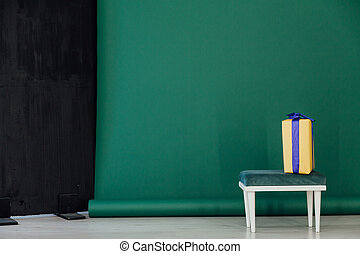 chair with a gift in the interior of the room on a green background