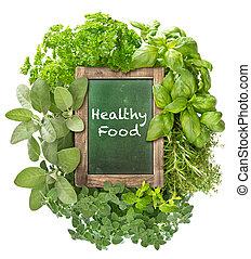 Green chalkboard with fresh herbs. Healthy Food