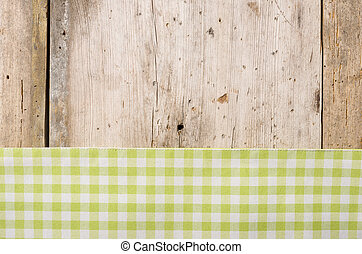 Green checkered tablecloth on a rustic wooden background