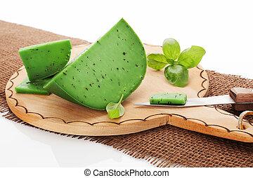 Green cheese gouda. - Green cheese gouda on wooden round...
