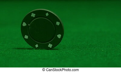 Green chip spinning on casino table in slow motion