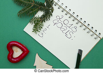 Green Christmas or New Year background with a notebook and a spruce branch