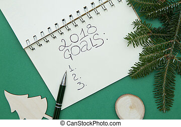 Green Christmas or New Year background with a notebook, wooden toys and a spruce branch