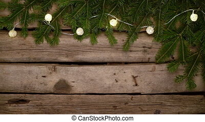 Green Christmas tree branches with lights on rough weathered...