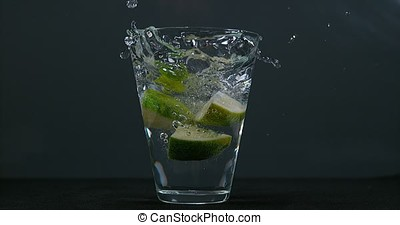 Green Citrus, citrus aurantifolia, falling into a Glass of...