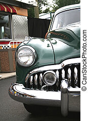 photograph of an old classic green car in mint condition shining chrome and highly polished finish absolutely beautiful