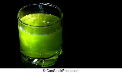 green cocktail in a glass on black background