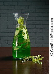 Green cold cocktail in a glass decanter on the table