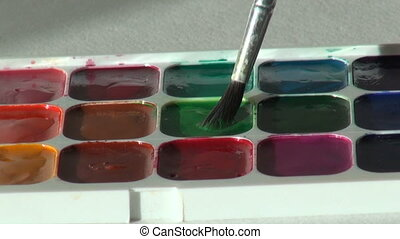 green color. close up. Artist works with brush and...