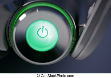 Green computer power on glowing button