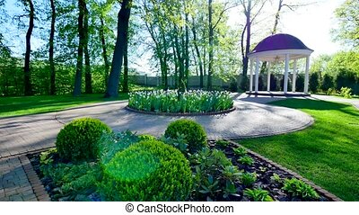 green courtyard with gazebo and flower beds.