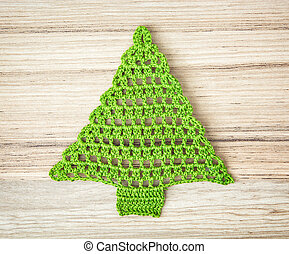 Green crochet christmas tree on the wooden background