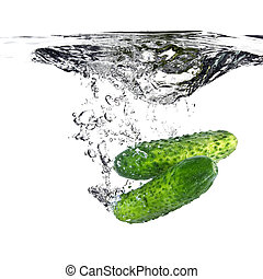 green cucumbers dropped into water isolated on white