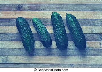 Green cucumbers on a cutting board
