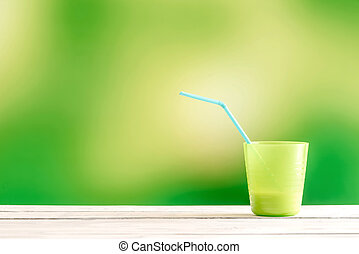 Green cup with a blue straw