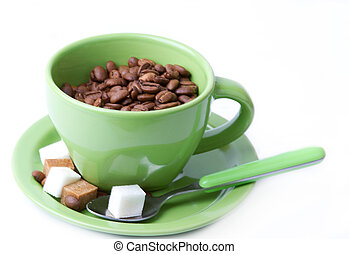 green cup with coffee beans and pieces
