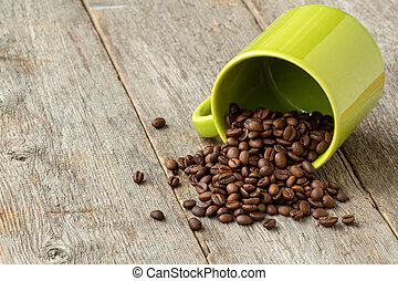 Green cup with scattered coffee beans
