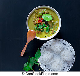 Green curry pork with thai rice vermicelli on black...