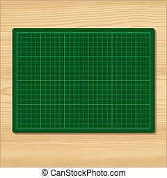 Green cutting mat isolated on wood background.