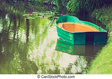 Green decorative wooden boat on lake water