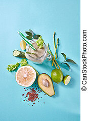 Green detox smoothies from avocado, selery, cucumber with flax seeds in a glass jar on a blue paper background.