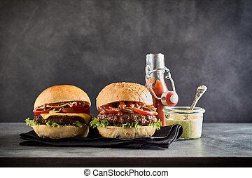 Green dipping sauce beside a cheese burger
