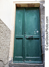 Green door with mailbox and bronze handles in the stone wall background.