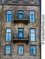 Green Doors and Balconies on Old Brick Building