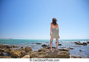 green dress woman on the rocks