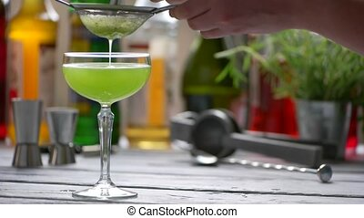 Green drink drips through sieve.