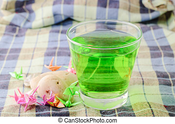 green drink on fabric texture and paper bird on table