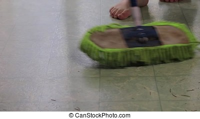green dust mop gliding along lenoleum - green dust mop...