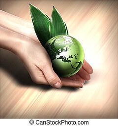 green earth with growing plant - human hands holding green...