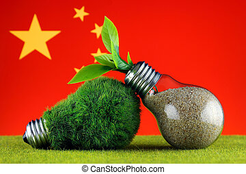 Green eco light bulb with grass, plant growing inside the light bulb, and China Flag. Renewable energy. Electricity prices, energy saving in the household.