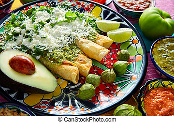 Green enchiladas Mexican food with guacamole and sauces on...