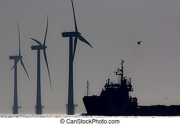 Green energy. Offshore wind farm turbines with ship at sea. Silhouette at dawn.